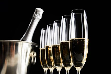 selective focus of champagne glasses with sparkling wine near ice bucket with bottle isolated on black Stockfoto