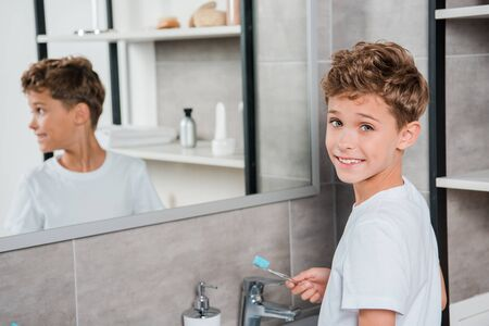 selective focus of cheerful boy holding toothbrush in bathroom 免版税图像