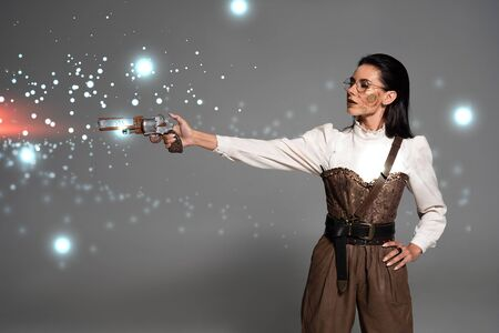steampunk woman shooting from revolver with hand on hip on grey background with glowing illustration