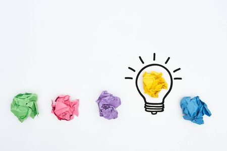top view of colorful crumpled paper balls and illustration of light bulb, business concept
