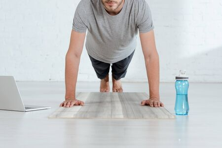 partial view of man practicing forearm plank pose near laptop and sports bottle