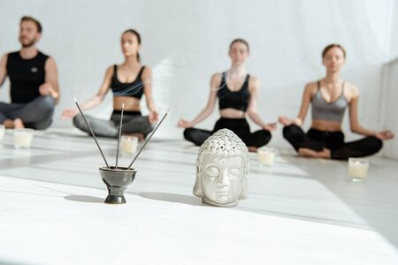 selective focus of decorative buddha head, aromatic sticks and candles, and young people practicing yoga in half lotus pose Banco de Imagens