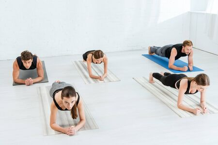five young people practicing yoga in forearm plank pose