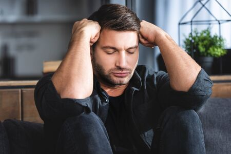 handsome man in black shirt with headache touching head in apartment