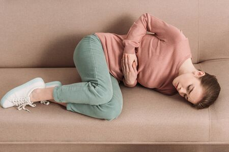 unhappy woman lying on sofa while suffering from stomach pain Reklamní fotografie