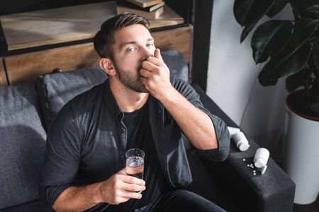 high angle view of handsome man with panic attack taking pills and holding glass of water in apartment Stok Fotoğraf