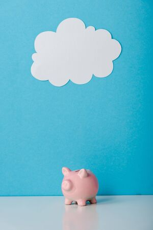 pink piggy bank near white cloud on blue with copy space