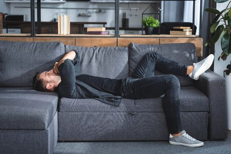 side view of handsome man with headache lying on sofa in apartment