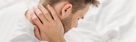 panoramic shot of young man suffering from neck pain