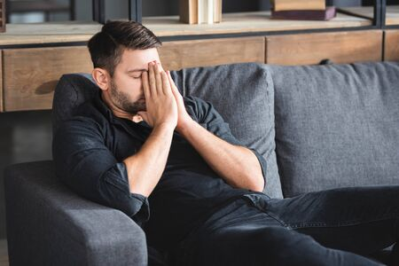 man with headache sitting on sofa and obscuring face in apartment