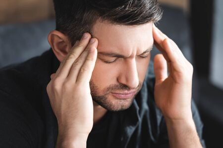 handsome man with headache touching head in apartment Reklamní fotografie