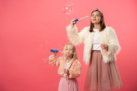 daughter and smiling mother blowing soap bubbles on pink background