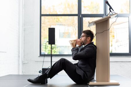 side view of scared businessman in suit breathing in paper bag during conference