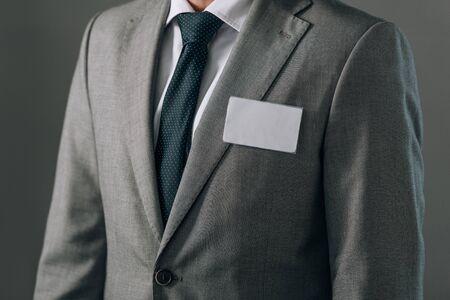 Vue recadrée de l'homme en costume avec badge isolé sur gris