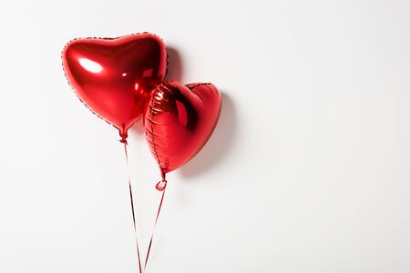 shiny and red heart shaped balloons on white