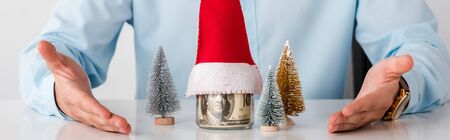 panoramic shot of man with pointing with hands at glass jar with money and santa hat isolated on white