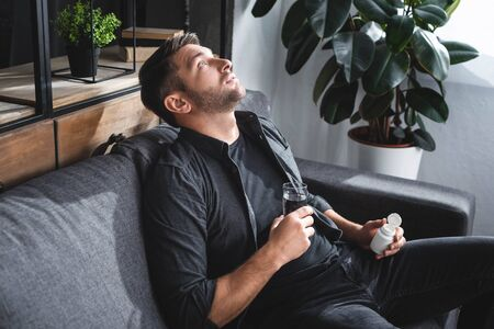 handsome man with panic attack holding pills and glass of water in apartment Stok Fotoğraf