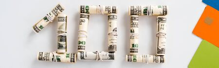 panoramic shot of one hundred dollar banknotes in cash rolls on white
