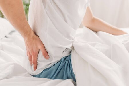 cropped view of man sitting on white bedding and suffering from loin pain