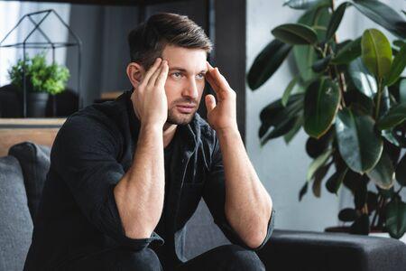handsome man in shirt with headache touching head in apartment Reklamní fotografie