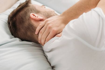 young man lying in bed and suffering from neck pain Reklamní fotografie