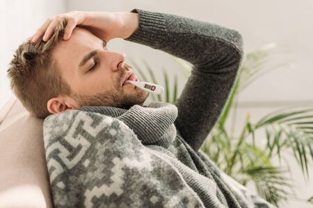 sick man, wrapped in blanket, sitting on sofa with closed eyes and measuring temperature Reklamní fotografie - 134985167