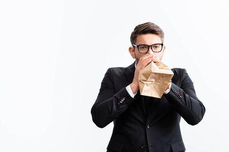 scared businessman in suit breathing in paper bag during conference isolated on white