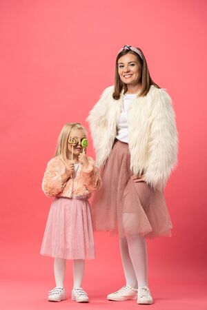 daughter obscuring face with lollipops and smiling mother looking at camera on pink background