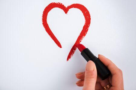 vista ritagliata della donna che disegna il cuore mentre tiene il rossetto rosso isolato su bianco