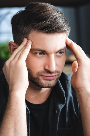handsome man with headache touching head and looking away in apartment Reklamní fotografie
