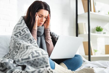 tired ill woman with headache having online consultation with doctor on laptop