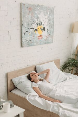young woman lying in bed and suffering from migraine