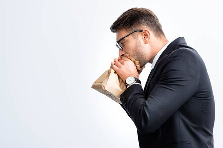 side view of scared businessman in suit breathing in paper bag during conference isolated on white