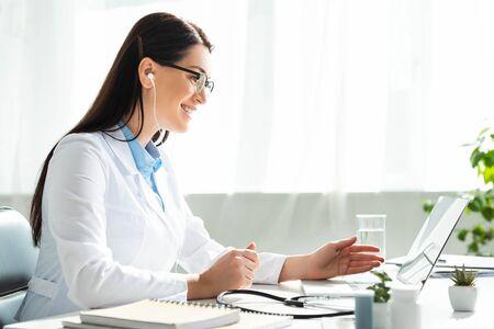 positieve arts in oortelefoons met online overleg met patiënt op laptop in kliniekkantoor Stockfoto