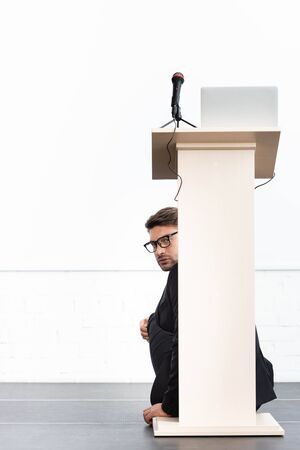 scared businessman in glasses hiding behind podium tribune during conference isolated on white Standard-Bild