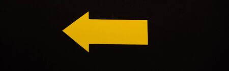 panoramic shot of yellow directional arrow isolated on black