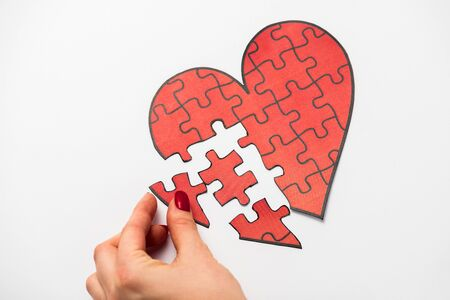 cropped view of woman touching drawn red heart shape jigsaw isolated on white
