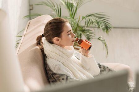 mise au point sélective d'une fille malade assise sur un canapé et buvant du sirop contre la toux