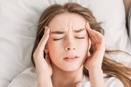 top view of young woman with closed eyes touching head while suffering from migraine