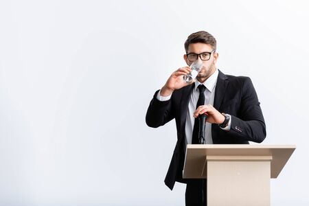 scared businessman in suit standing at podium tribune and drinking water during conference isolated on white