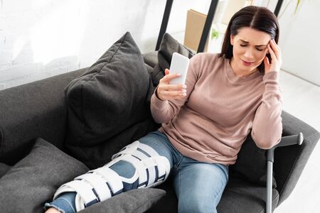 stressed woman with headache and broken leg having online consultation with doctor on smartphone at home Reklamní fotografie - 134984592
