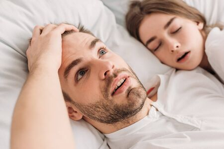 awakened man holding hand on head while lying in bed near snoring wife Reklamní fotografie - 134984599
