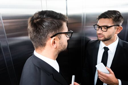 high angle view of businessman in suit looking at mirror in elevator Фото со стока