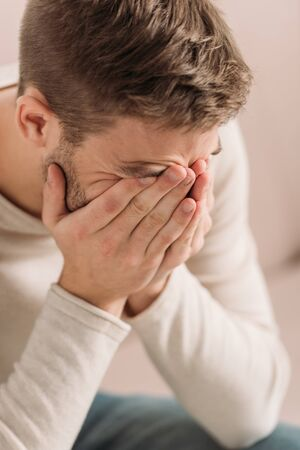 young man covering face with hands while suffering from migraine