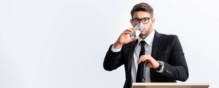 panoramic shot of scared businessman in suit standing at podium tribune and drinking water during conference isolated on white