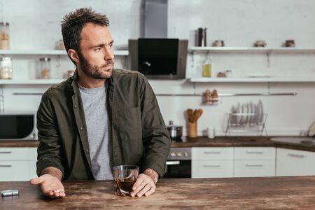 Uomo triste che tiene in mano un bicchiere di whisky e pillole sul tavolo della cucina kitchen Archivio Fotografico