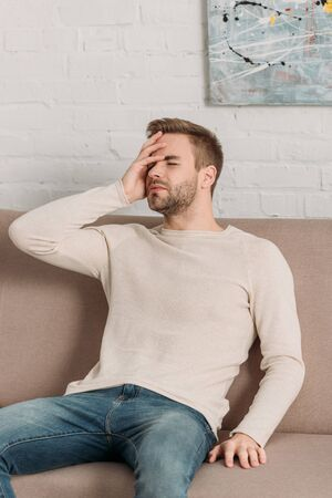 young man sitting on sofa with closed eyes while suffering from migraine Reklamní fotografie