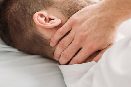 cropped view of young man touching neck while suffering from pain
