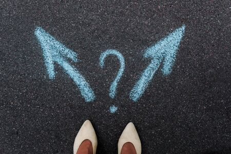 top view of woman standing near blue directional arrows and question mark on asphalt