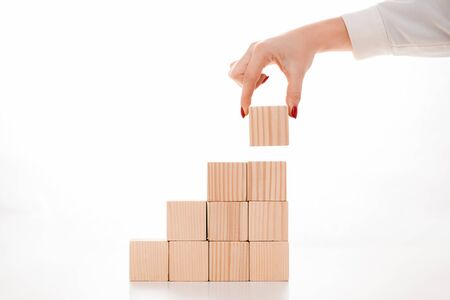 cropped view of businesswoman holding wooden cube on white